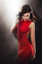 Karaoke Party. Beautiful Singing Girl. Woman in red with Microphone Royalty Free Stock Photo