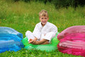 Karate boy sits in inflatable armchair  on lawn Royalty Free Stock Photo