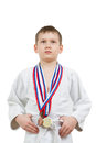 Karate boy in white kimono with medals fighting Royalty Free Stock Photo