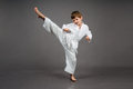 Karate boy in white kimono studio portrait of a pose wearing with grey background Stock Photography