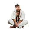 Karate fighter with crossed legs fat sits over white Stock Image
