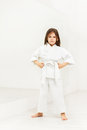 Karate girl standing with hands on hips in gym Royalty Free Stock Photo