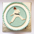 Karate kid cake birthday decorated with silhouette in blue and white on gray background Stock Images
