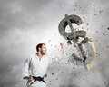 Karate man in white kimino young determined breaking with hand concrete dollar sign Royalty Free Stock Images