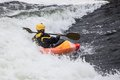 Kayaker an active male rolling and surfing in rough water Stock Photo