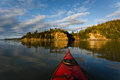 Kayaker heads toward land in remote alaskan wilderness on sunny afternoon summer Stock Photo