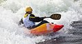 Kayaking an active male kayaker rolling and surfing in rough water Royalty Free Stock Photos