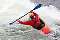 Kayaking an active male kayaker rolling and surfing in rough water Stock Photos