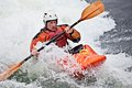 Kayaking an active male kayaker rolling and surfing in rough water Stock Photography