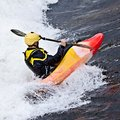 Kayaking an active male kayaker rolling and surfing in rough water Stock Image
