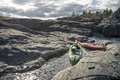 Kayaks stand moored on a rocky shore, in the background there is Royalty Free Stock Photo
