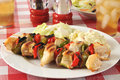 Kebabs on a picnic table chicken shish with potato salad Royalty Free Stock Images
