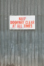 Keep clear a doorway sign mounted to a metal wall Royalty Free Stock Photo