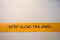 Keep clear warning sign in yellow banner on the floor, with copy space Royalty Free Stock Photo