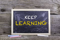 Keep Learning. Chalk board on a wooden table Royalty Free Stock Photo