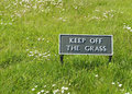 Keep off the grass sign green painted enamel on a lawn of bright green with wild daisies Stock Photo