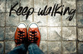 Keep walking word on pavement with shoes background, Inspiration quote Royalty Free Stock Photo