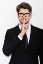Keeping business secrets serious young man in formalwear holding finger on lips and looking at camera while standing against white Royalty Free Stock Photography