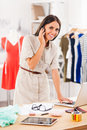 Keeping everything under control happy young woman talking on the mobile phone and working on laptop while standing in fashion Royalty Free Stock Photo
