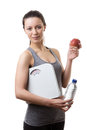 Keeping fit and healthy woman standing dressed ready to go down the gym holding scales an apple a bottle of water Royalty Free Stock Photos
