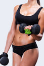 Keeping her body strong and healthy close up of young sporty woman exercising with dumbbells while standing against grey Royalty Free Stock Image