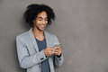 Keeping in touch cheerful young african man holding smart phone and looking at it with smile while standing against grey Stock Image