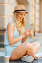 Keeping in touch with her friends side view of young woman holding mobile phone and smiling while sitting outdoors Royalty Free Stock Photo
