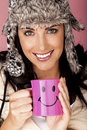 Keeping warm a beautiful woman wearing a fur hat and holding a drink on a pink background Royalty Free Stock Image