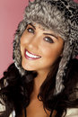 Keeping warm a beautiful woman wearing a fur hat on a pink background Royalty Free Stock Image