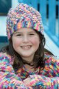 Keeping warm in winter headshot portrait of pretty smiling little girl with multicoloured beanie and woolly jumper to keep Royalty Free Stock Images