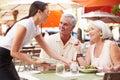 Kellnerin serving senior couple mittagessen restaurant im im freien Lizenzfreie Stockfotografie