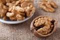 Kernels of nuts in plate and walnut on sackcloth Royalty Free Stock Photo