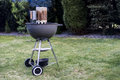 Kettle barbecue charcoal grill roasting BBQ standing on gras ready for action Royalty Free Stock Photo