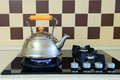 Kettle basking in the modern gas stove heats interior of kitchen Royalty Free Stock Photography