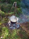 Kettle on campfire with boiling water tripod over Royalty Free Stock Photography