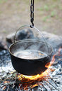 Kettle on fire cooking food in the forest camping Stock Image
