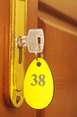 Key in keyhole with numbered label door handles on wood wing of door and Stock Photo