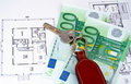 Key and money on home plan Royalty Free Stock Photo