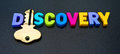 Key to discovery text in colorful uppercase letters with letter i replaced by gold dark background Stock Photography