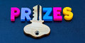 Key to prizes text in colorful uppercase letters with letter i replaced by a golden dark background Stock Photo