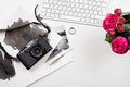 Keyboard, pink flowers and photo camera on white table, photogra Royalty Free Stock Photo