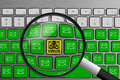 Keyboard with yellow email virus button surrounded with green email buttons and magnifying glass Royalty Free Stock Photo