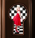 Keyhole retro fashion portrait of stylish girl a sensual pinup dancing in bright red dress image view through door Stock Photography