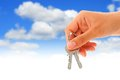 Keys in hand over sky background Stock Photo