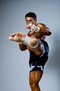 Kick-boxer kicks on a gray background. Stock Image