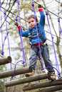 Kid in adventure park walking on tree logs Royalty Free Stock Photo