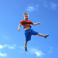 Kid in the air with sky background Royalty Free Stock Photography