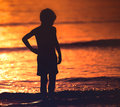 Kid alone silhouette thought full looking to sea Stock Photos