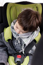 Kid asleep in the car seat with safety belt and head leaning side Royalty Free Stock Image