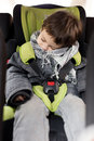 Kid asleep in the car seat with safety belt and head leaning side Stock Photo
